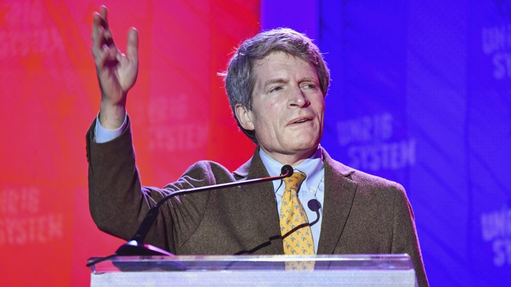 Richard Painter waves his hand as he speaks to a crowd.