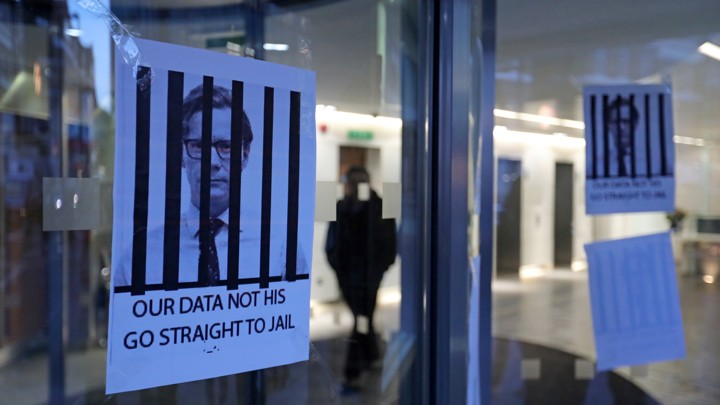 "Posters hang on a glass door depicting the Alexander Nix behind bars with the text, ""Our Data Not His. Go Straight to Jail."""