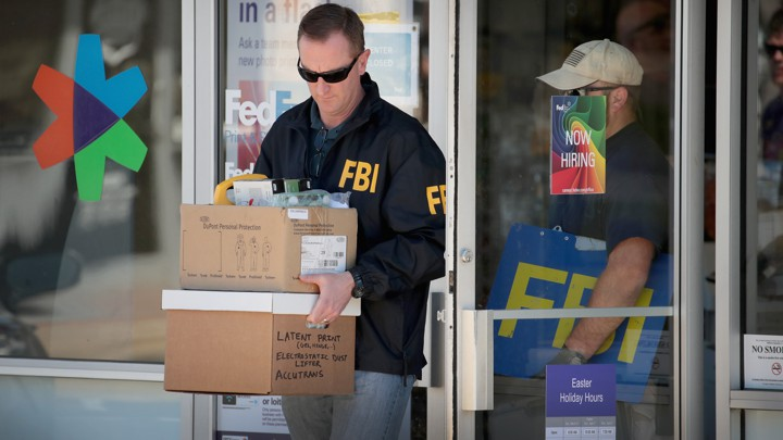 A man in an FBI jacket carries boxes out of a FedEx center.