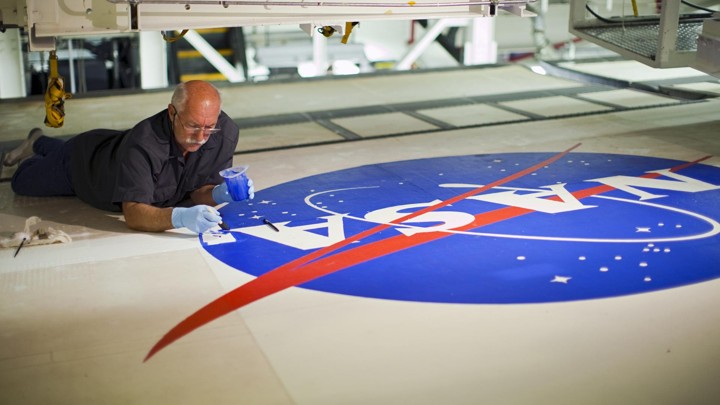A person lies on a surface while painting a large NASA logo.