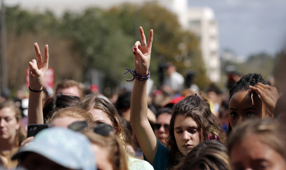 People raise their hands in peace signs at a rally.