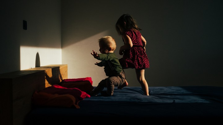 Two children playing on a bed