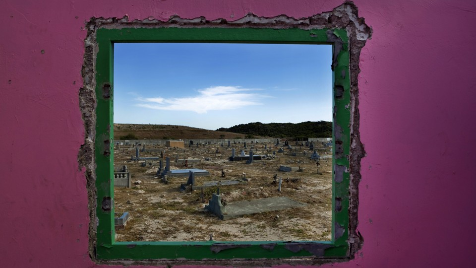 Graves seen through a window in Cape Town's Khayelitsha township
