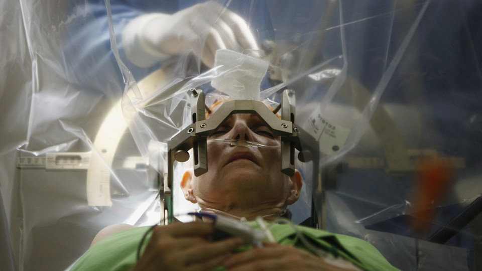 A patient lies on an operating table in front of a plastic sheet, behind which a person in scrubs and gloves performs surgery on the patient's brain.