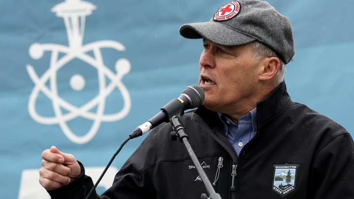 Washington Governor Jay Inslee speaks into a microphone in front of a banner showing an atom and the Seattle Space Needle.