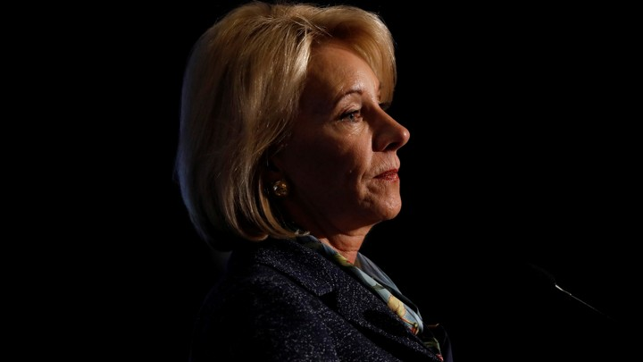 Betsy DeVos speaking at podium against a black background