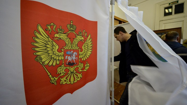 A man enters a polling booth in Russia's 2018 presidential elections.