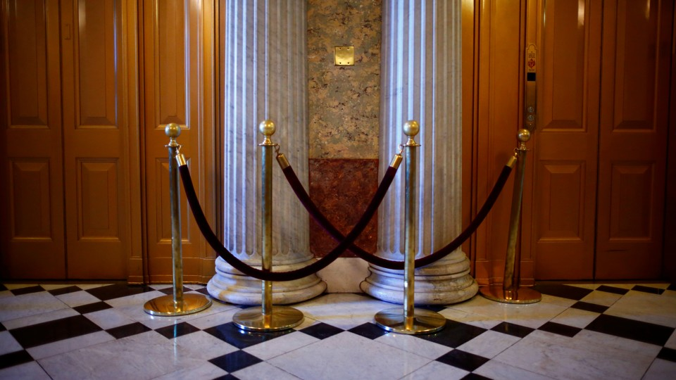 Columns, doors, and crowd-control rope barriers inside the Capitol