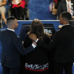 A view from behind of Christine Leinonen speaking at a podium, with Juan Arriagada and Brandon Wolf holding her shoulders