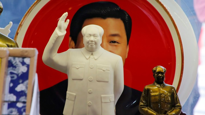 Sculptures of the late Chinese Chairman Mao Zedong in front of a souvenir plate featuring a portrait of Chinese President Xi Jinping at a shop next to Tiananmen Square in Beijing, China, on March 1, 2018.
