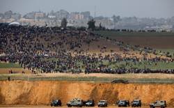 Israeli military vehicles are seen Friday next to the border on the Israeli side of the Israel-Gaza border, as Palestinians demonstrate in Gaza.