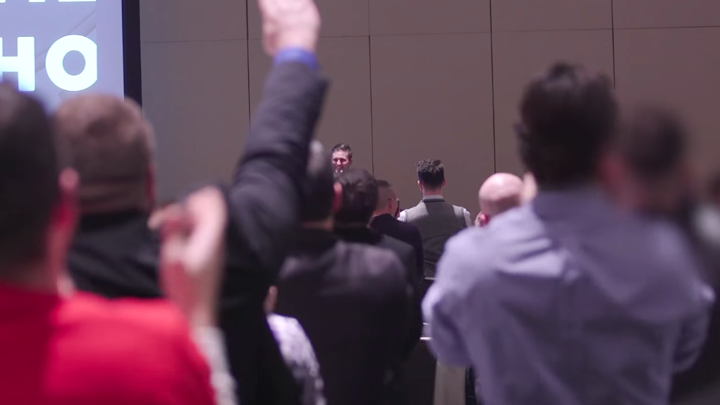 A crowd of white men seen from behind, one of whom has raised his arm in a Nazi-style salute