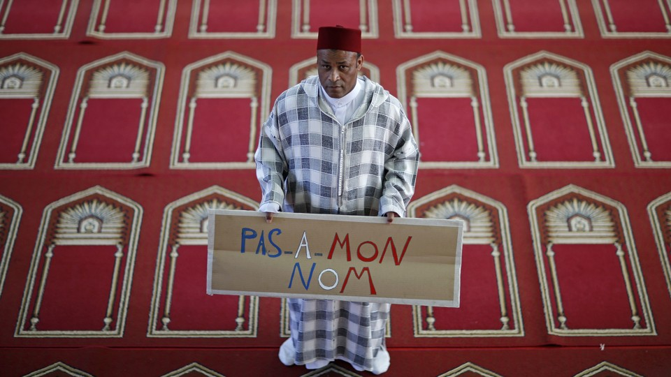 "Khaloar Abdarahim holds a placard reading ""Not in my name"" as he poses inside the Arrahma Mosque in Nantes, France, in 2014."