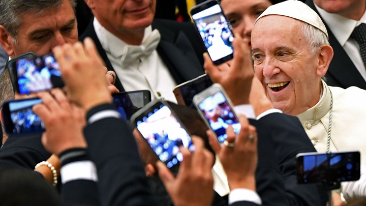 Pope Francis arrives to lead his weekly general audience in 2016 at the Vatican as people take pictures of him.