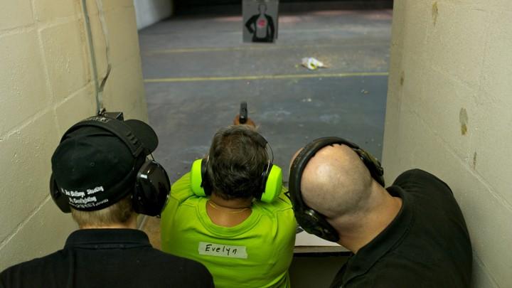 A person shoots a gun at a target.