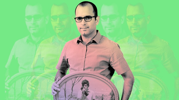 Yaniv Erlich holding a photo of his father as a teenager against a green background