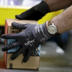 A person wearing a watch and gloves handles an Amazon package.