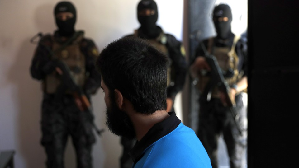 Kurdish soldiers from the Anti-Terrorism Units stand in front a suspected Islamic State member