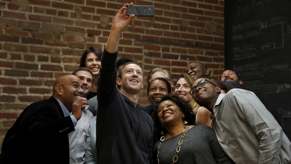 Mark Zuckerberg taking a selfie with a group of people