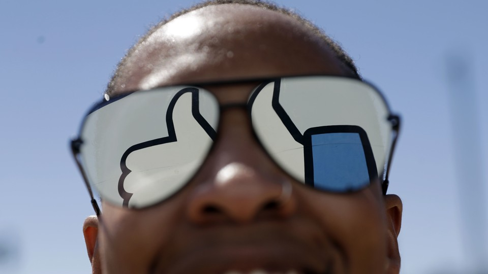 """The Facebook """"like"""" symbol reflected in a person's sunglasses"""
