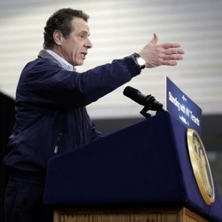 New York Governor Andrew Cuomo giving a speech at a lectern