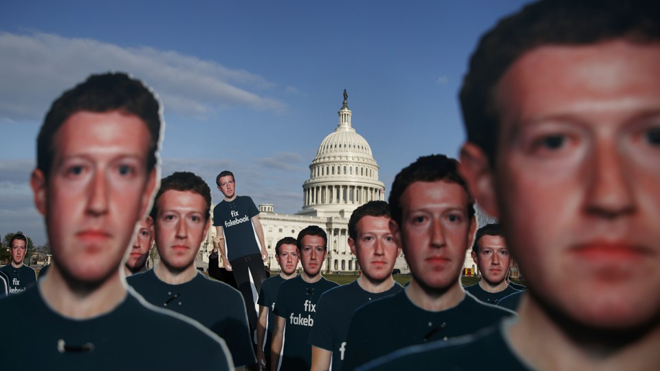 Cardboard cutouts of Mark Zuckerberg's face dominate the foreground, while the dome of the U.S. Capitol looms in the background.