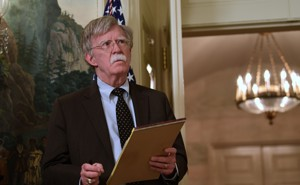 John Bolton holding a legal pad