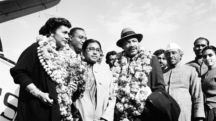 Martin Luther King, Jr. and his wife Coretta, both wearing garlands, are received by admirers after landing at the airport in New Delhi, India, in 1959.