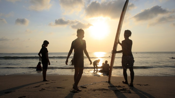 Figures on a beach at sunset
