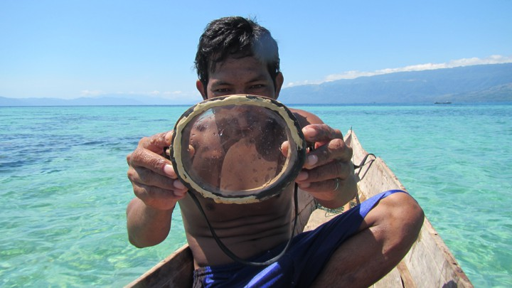 A Bajau diver holds up his wooden diving mask.