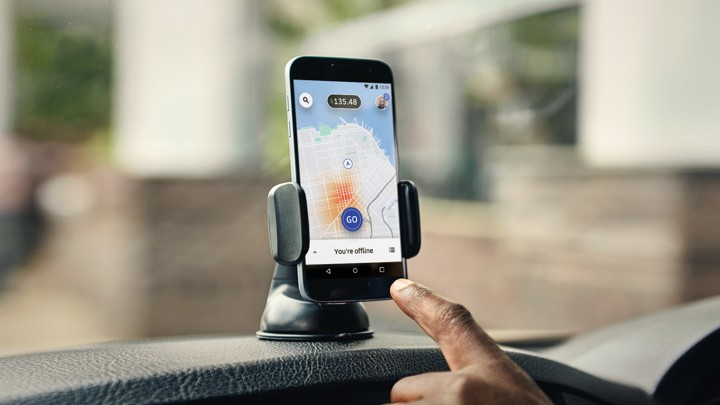 A hand pointing to a smartphone with Uber's app open