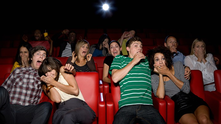 A group of people in a movie theater make scared faces and clutch each other.