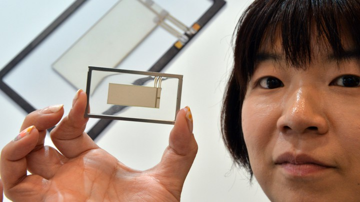 A woman holds a small, thin piezoelectric speaker