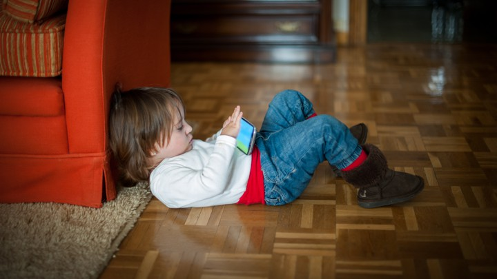 A child on the floor looking at a smartphone