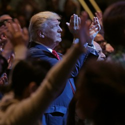 Donald Trump, standing among a group of churchgoers, claps during a worship service in Las Vegas.