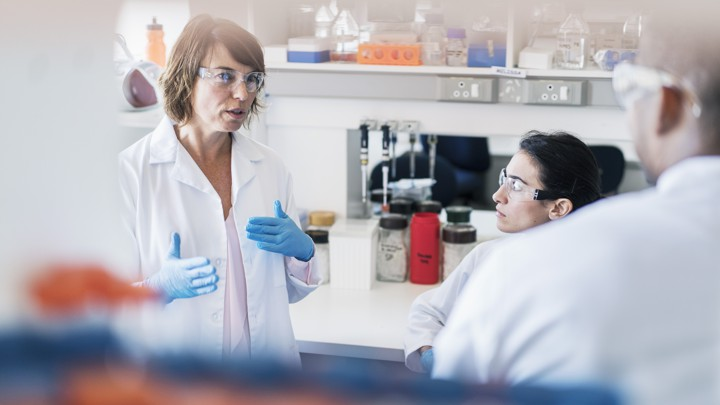 A woman wearing a lab coat, lab goggles, and plastic gloves, speaks and gestures.