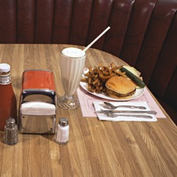 A table at a diner with a hamburger, french fries, milkshakes, and ketchup