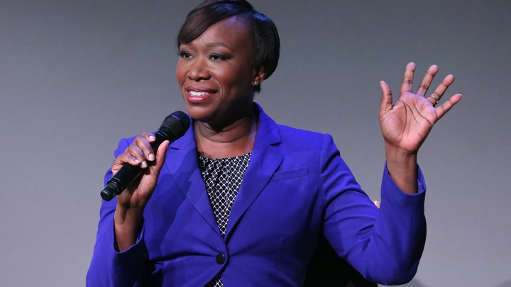 Joy Reid wearing a purple blazer and holding a microphone