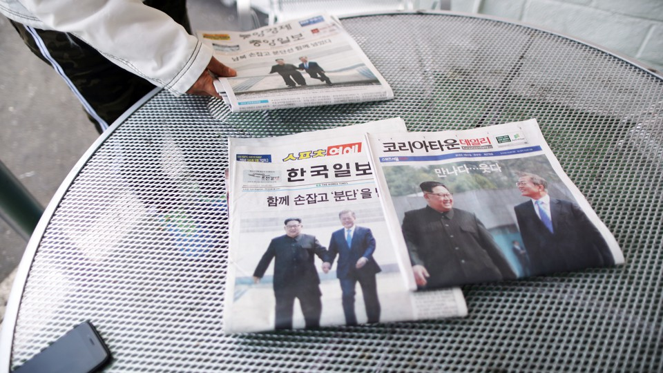 Korean newspapers on a table showing Presidents Kim and Moon together
