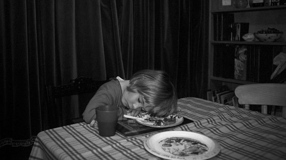 A black-and-white photo of a young girl asleep at the dinner table