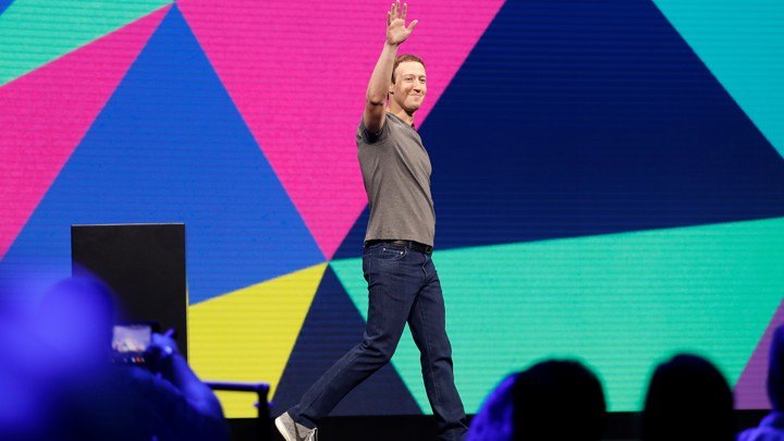 Mark Zuckerberg raises his hand while walking across a stage.