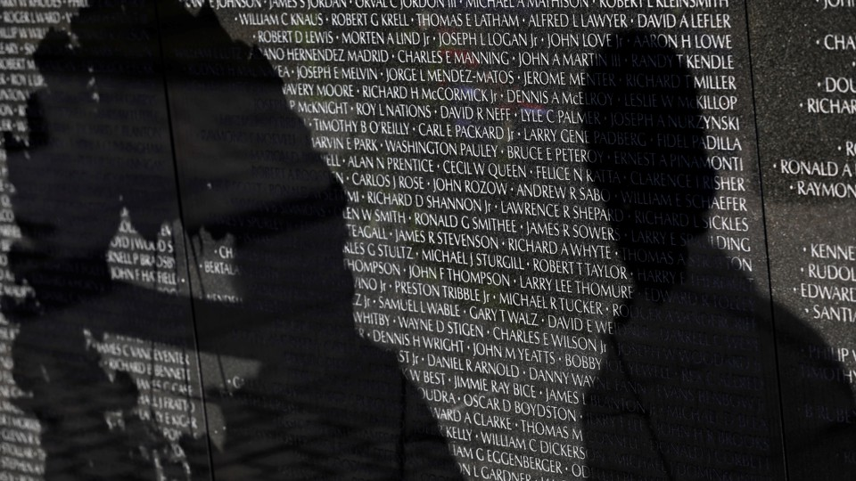 Visitors' shadows are seen cast on the Vietnam Veterans Memorial wall