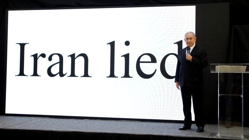 "Prime Minister Netanyahu in front of a screen that reads ""Iran lied"""