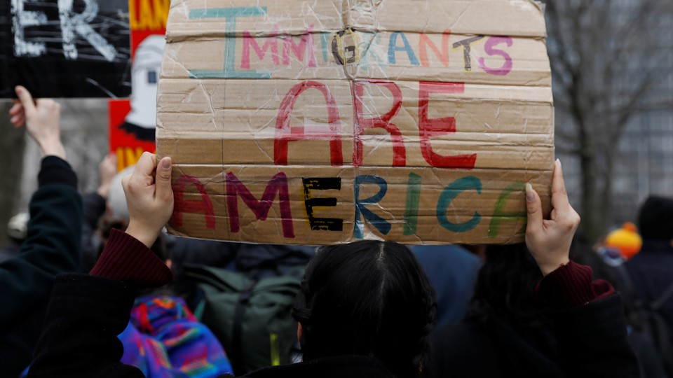 "Hands holding a colorful sign that reads ""Immigrants Are America"""