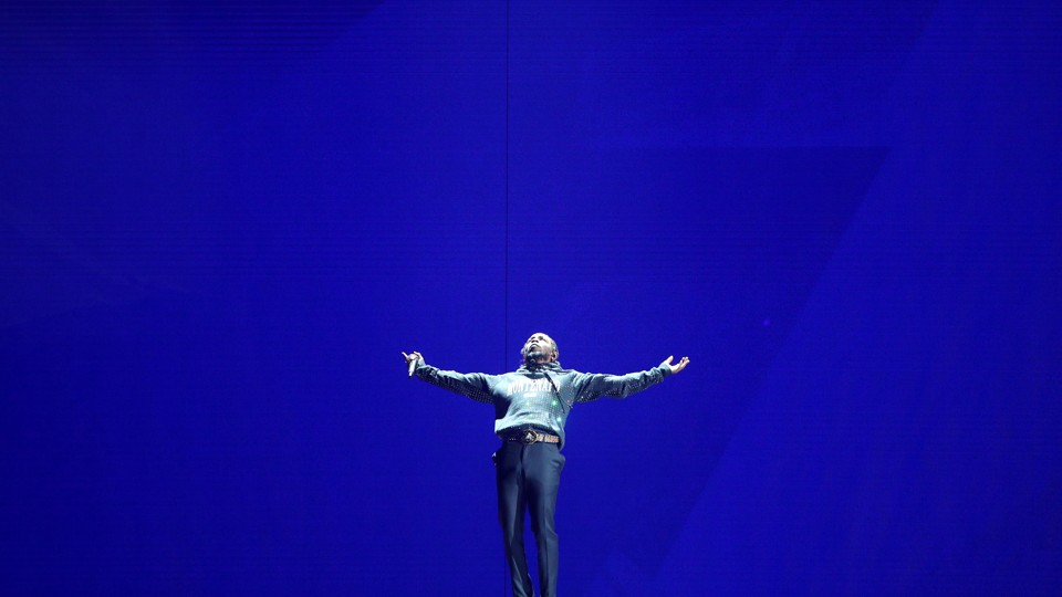 Kendrick Lamar performing onstage against a blue backdrop