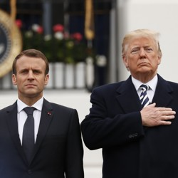 Macron standing with arms at sides next to Trump, who has a hand over his heart