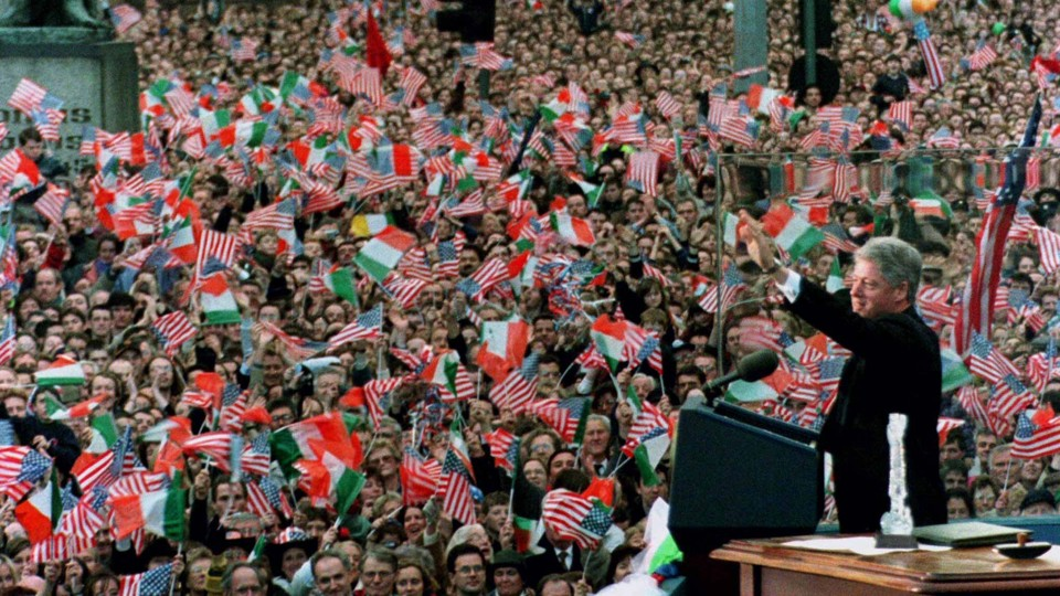Former President Bill Clinton waves to a large crowd waving Irish and American flags in Dublin.