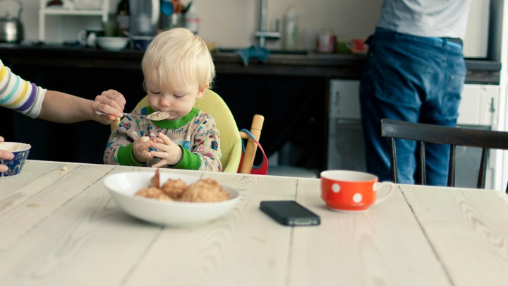 A mother spoon-feeds an infant while a man stands at a kitchen counter