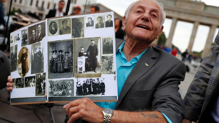 Holocaust survivor Morris Dan shows family photographs as he poses in front of the Brandenburg Gate in Berlin in 2017.