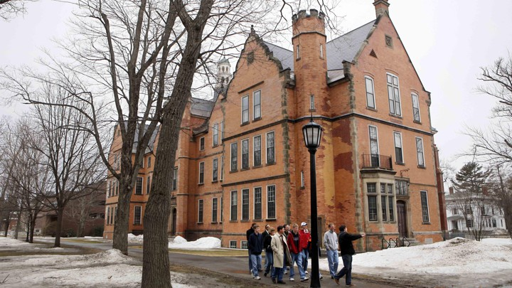 A photo of people walking by a Bowdoin, College campus building.